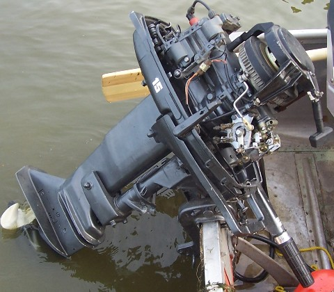 old 15 hp outboard with cover off of it.